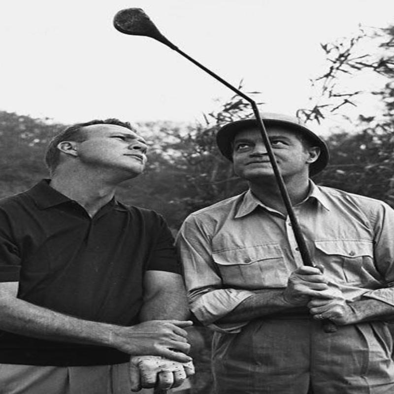 Bob Hope shows a bent golf club to the golfer…